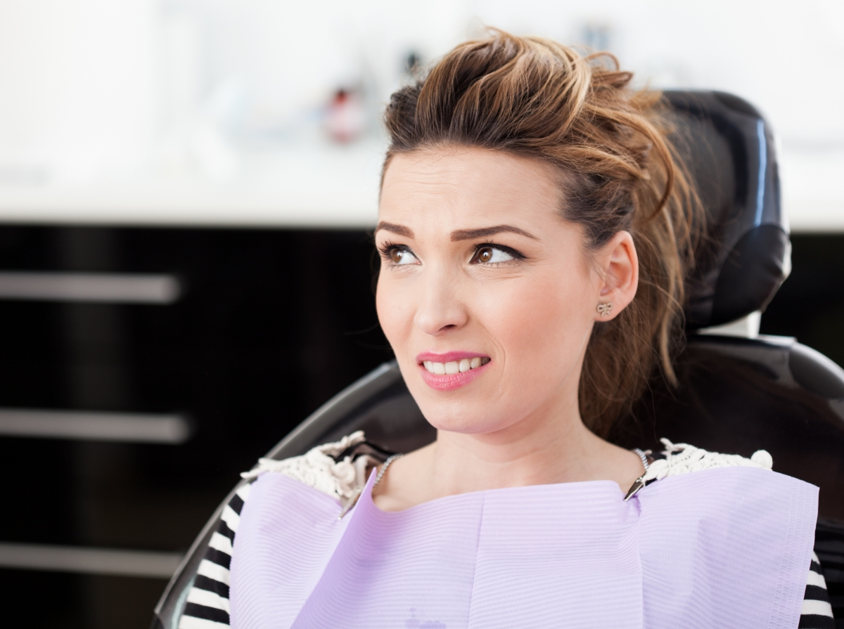 Woman in Dentist Chair Looking Apprehensive