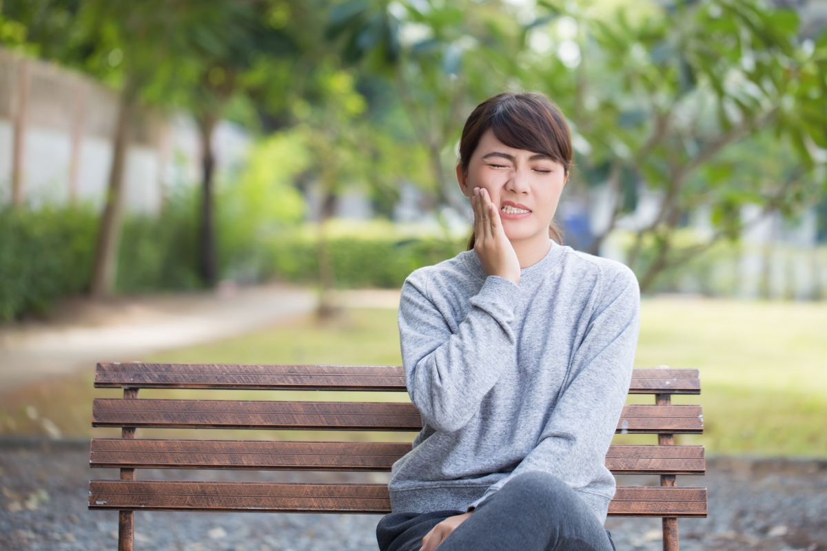 Woman with TMJ pain on park bench